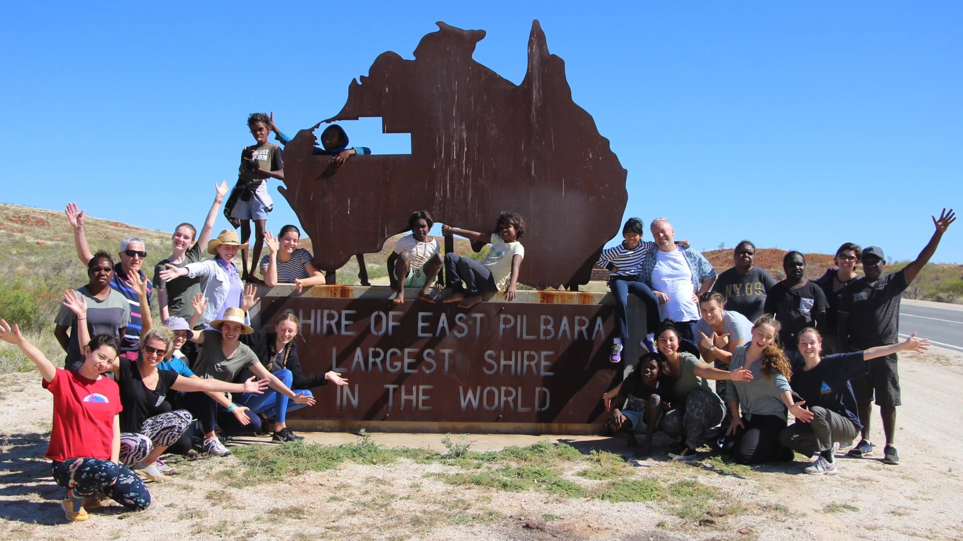 Group Waving to the Camera by the Large East Pilbara Shire Signage